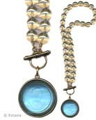 Transparent Aqua German Glass intaglio pendant on Champagne Czech glass hand knotted beading. Large pendant is 1 1/2 inches in diameter on 17 inch long beaded necklace. Front toggle closure. Shown in our signature Bronze metal. Each necklace made to order in the USA from the worlds finest materials.