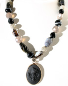 Our stunning jet German glass cameo on a single hand-knotted strand of mixed semi-precious stones. (Black Onyx, Grey Onyx, Labradorite, Sardonyx). Beautiful opaque cameo is of Venus, from Greek mythology, often pictured with a dove, as shown here. Medium sized pendant measures 1 1/4 by 3/4 inch. Necklace is 17 inches with a 3 inch adjustor to equal 20 inches. Red Bronze.