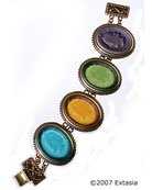 Bracelet in a beautiful jeweltone color combination of Zircon, Citrine, Olivine and Eggplant German glass cameos. The cameos are of images from Greek mythology, glass is slightly transparent. Cameos in their settings measure 1 1/2 by 1 1/4 inches. Very pretty combination in one of our more popular new bracelets. Red Bronze. Each bracelet made to order in the U.S.A.