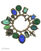 Our over the top charm bracelet. Shown here in a mix of blues and greens. 15 hand pressed German glass cameos and intaglios and cameos. Measures almost 8 inches in length. Largest charm is 1 1/4 by 7/8 inch. Bronze, each bracelet made to order in the USA from the worlds finest materials.