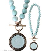 From our Scala Collection, a transparent Aqua German glass intaglio pendant on hand knotted strand of semi precious faceted beads. Large pendant is 1 1/2 inches in diameter. 18 inches in length. Shown in our signature Bronze metal. Each necklace made to order in the USA.