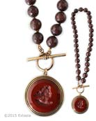 From our fall Scala Collection, an opaque Marsala German glass intaglio pendant on hand knotted strand of semi precious faceted Brown Jade.  Large pendant is 1 1/2 inches in diameter. Beautiful strand of Jade is 23 inches in length. Shown in our signature Bronze metal. Each necklace made to order in the USA.